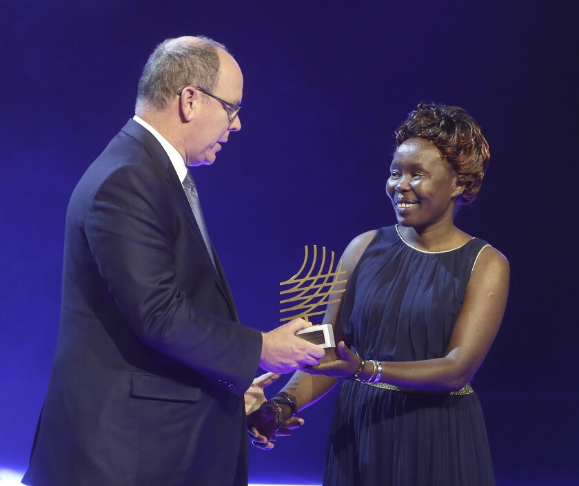 FILE - In this Friday, Dec. 2, 2016 file photo Prince Albert II of Monaco, left, presents Kenyan distance runner Tegla Loroupe with the 2016 President Award at the 2016 World Athletics Gala Awards in Monaco. Laroupe, currently the chief of mission for the IOC's Refugee Olympic Team, has tested positive for COVID-19, two people with knowledge of her condition have told The Associated Press. (AP Photo/Claude Paris)