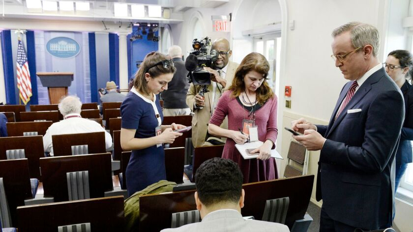 Reporters stand in the press briefing room of the White House after being excluded from the meeting on Friday.