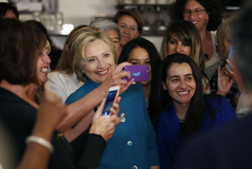 Democratic presidential candidate Hillary Clinton poses for photos with supporters at an event at a restaurant, Saturday, June 4, 2016, in Santa Barbara, Calif. (AP Photo/John Locher)