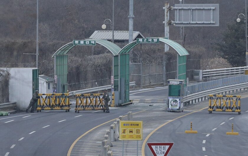 South Korean Army soldiers move barricades to close the road at the customs, immigration and quarantine office near the border village of Panmunjom in Paju, South Korea, Thursday, Feb. 11, 2016. North Korea on Thursday ordered a military takeover of a factory park that was the last major symbol of