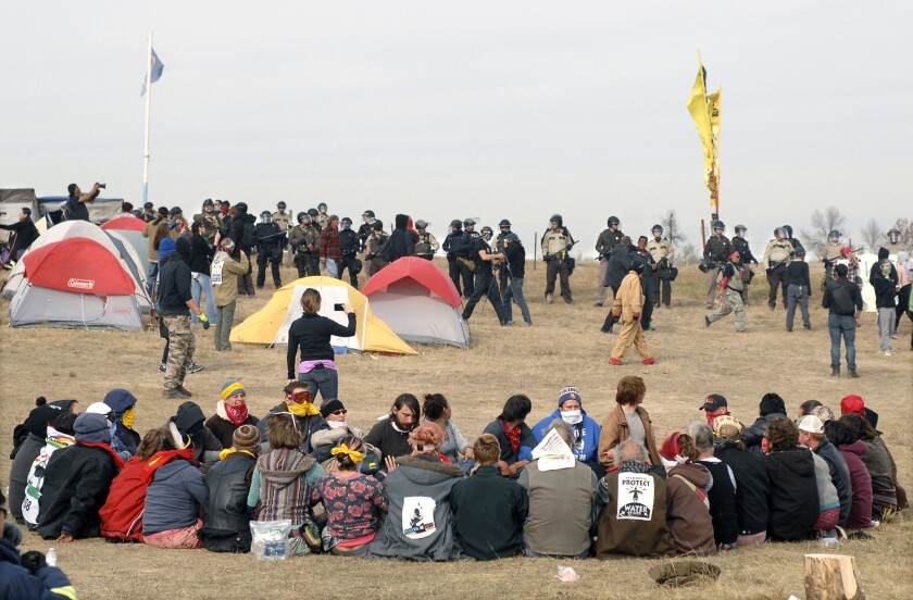Dakota Access pipeline protesters sit in a prayer circle as law enforcement officers prepare to remove them on Oct. 27, 2016.