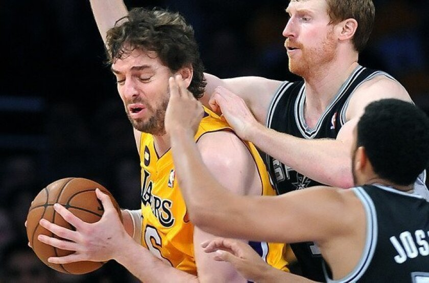 Lakers power forward Pau Gasol is swarmed by the double-team defense of Spurs forward Matt Bonner and guard Cory Joseph on Friday night at Staples Center.