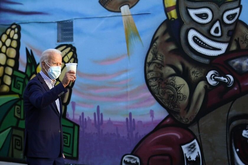 """Joe Biden """"toasts"""" supporters with a drink he received during a visit to the Barrio Cafe in Phoenix on Thursday."""
