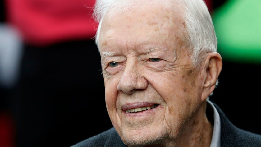FILE - In this Oct. 23, 2016, file photo, former President Jimmy Carter sits on the Atlanta Falcons