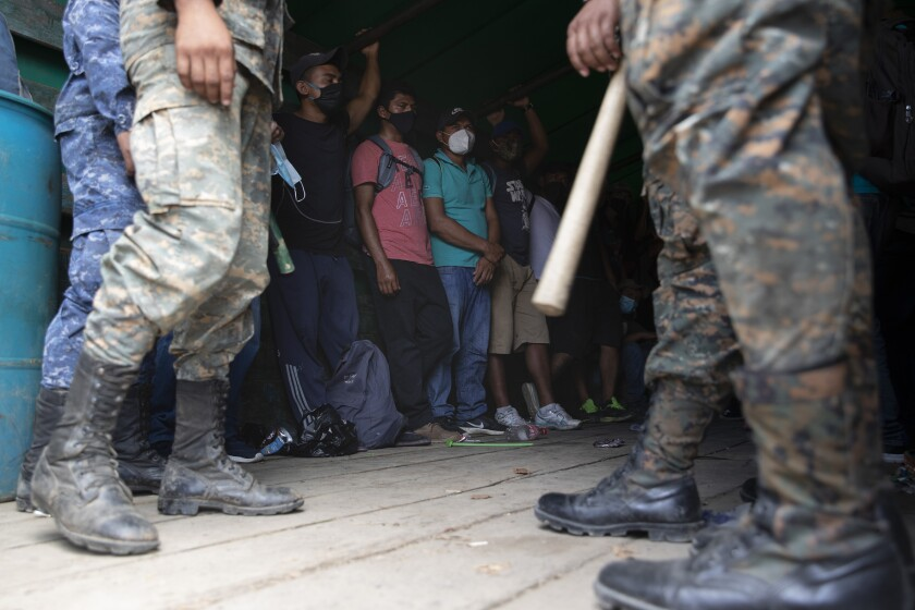 Honduras migrants stand in an army truck before returning home, in Morales, Guatemala, Saturday, Oct. 3, 2020. Early Saturday, hundreds of migrants who had entered Guatemala this week without registering were being bused back to their country's border by authorities after running into a large roadblock. (AP Photo/Moises Castillo)