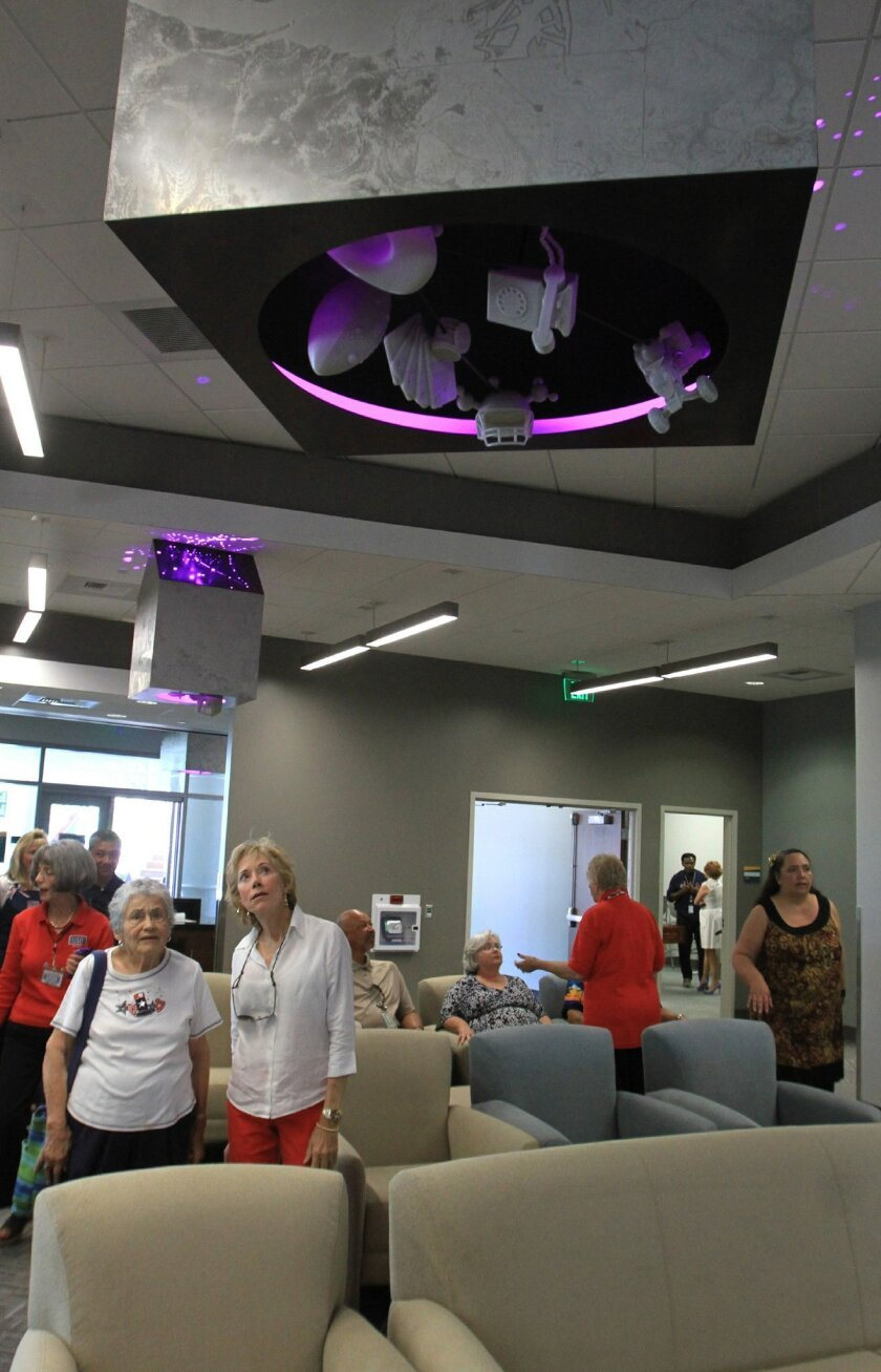 USO volunteers Grace Johnson, left in white, and Suzanne Richardson, next to her, look at public art on the ceiling at the new USO facility at San Diego International Airport.