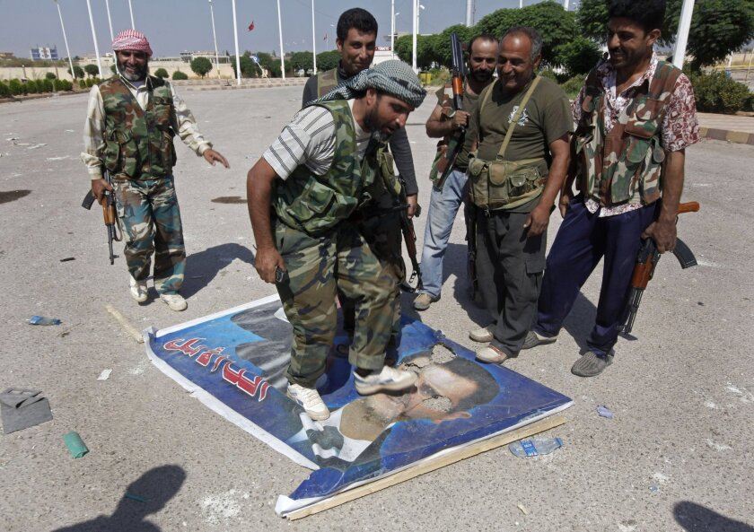 A Free Syrian Army fighter steps on a portrait of Syrian President Bashar Assad.