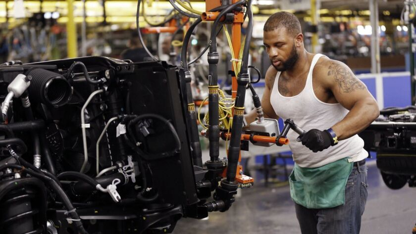 Stephen Carpenter works on an SUV at the General Motors plant in Arlington, Texas.