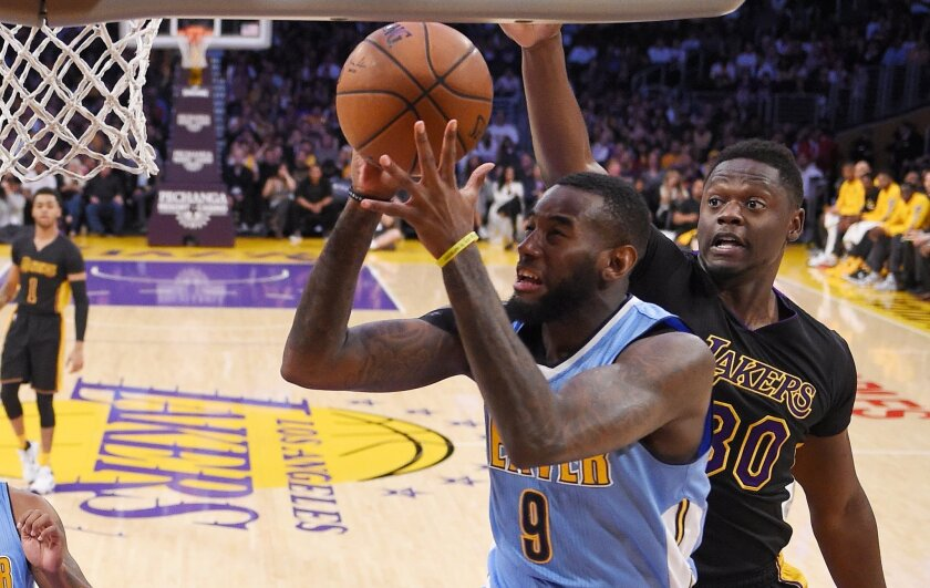 Denver Nuggets guard JaKarr Sampson shoots as Los Angeles Lakers forward Julius Randle defends during the first half of an NBA basketball game, Friday, March 25, 2016, in Los Angeles. AP Photo/Mark J. Terrill)