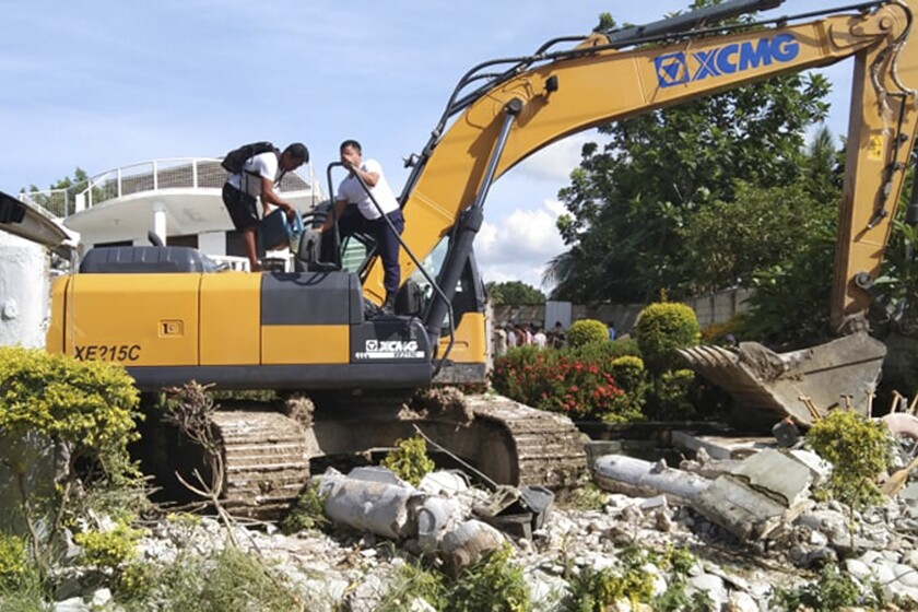 Men refuel a backhoe being used to sift through the rubble after a strong earthquake in central Philippines.
