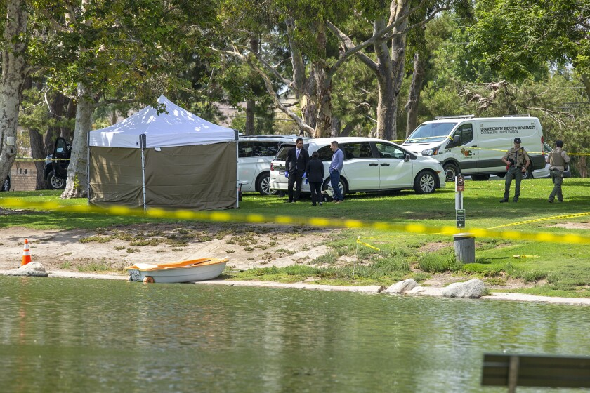 Sheriff's and OC Parks' personnel on Friday survey North Lake at Mile Square Park in Fountain Valley, where a body was found.