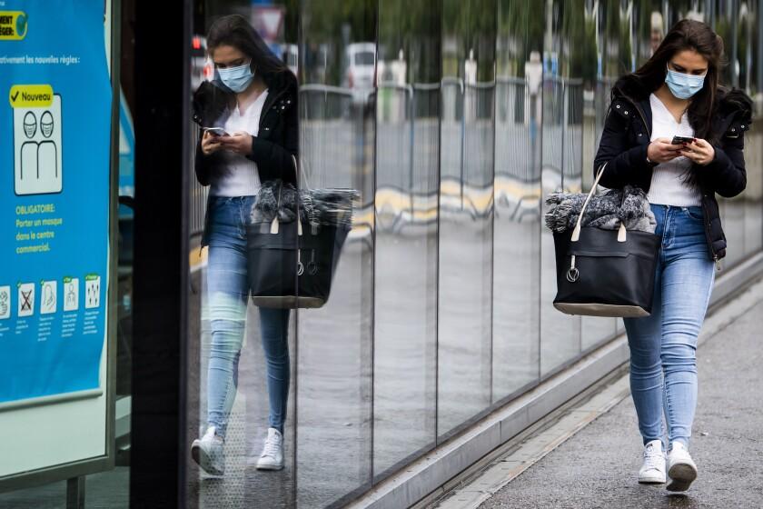 Una mujer usando un cubrebocas por el coronavirus camina por una calle en Fribourg, Suiza,