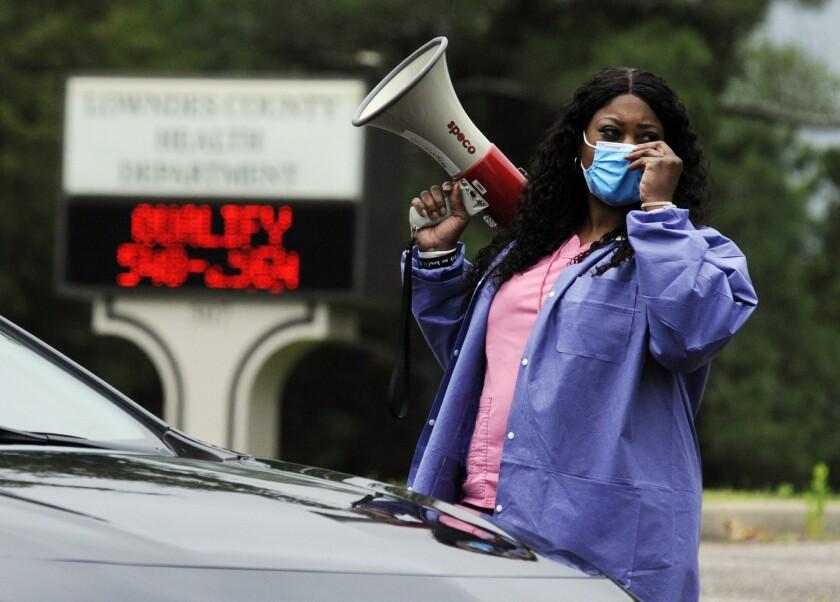 Healthcare worker Tonya Wilkes adjusts her mask at a testing site in Hayneville, Ala.