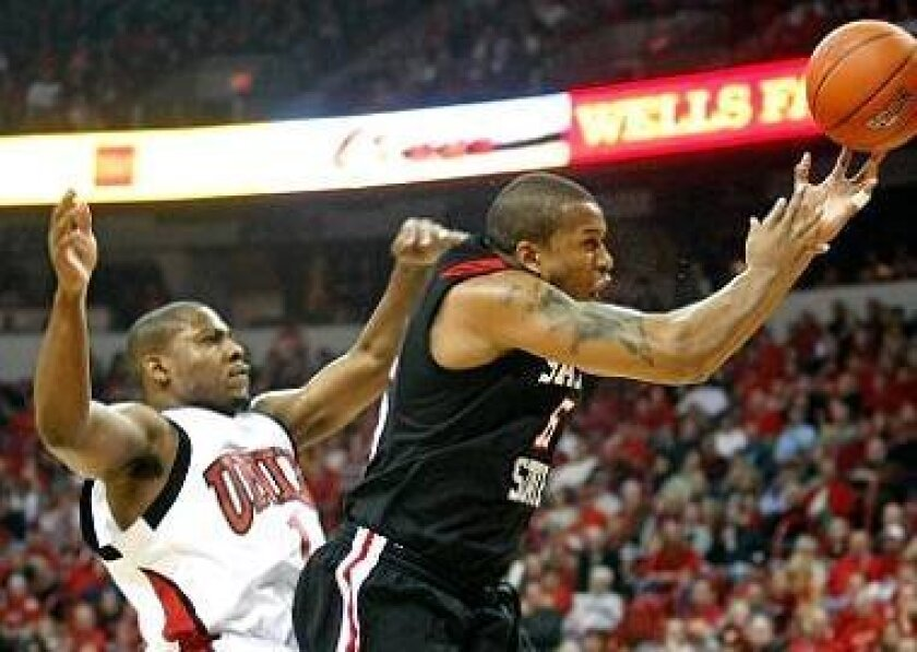Kyle Spain, being fouled by UNLV's Wink Adams, scored most of his points in overtime to lead the Aztecs.