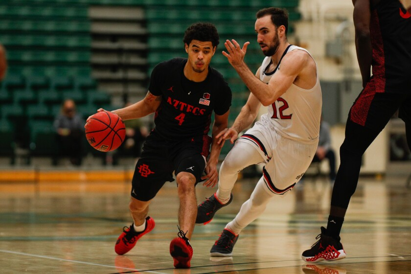 SSDSU's Trey Pulliam (4) dribbles against St. Mary's guard Tommy Kuhse in a 74-49 Aztecs win last season at Cal Poly.