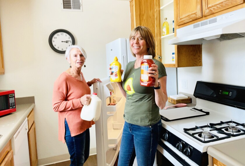 Soroptimists Pam Warnock and Vicki Jones stocking the kitchen in an apartment before a family moves in.