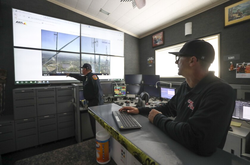 Cal Fire Capt. Kevin Cox points to the screen as he and Capt. Ryan Silva demonstrate the use of wildfire surveillance cameras while in the emergency command center at the Cal Fire San Diego Unit Headquarters on Wednesday.