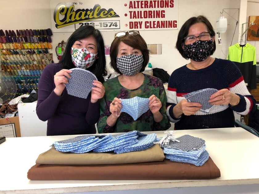 Employees and owner at Charles Alterations & Tailoring in Normal Heights hold up masks.