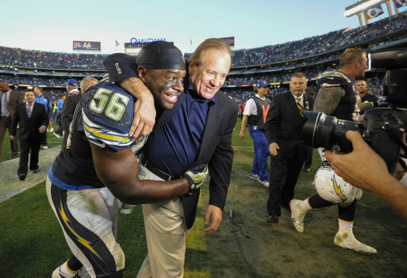 San Diego Chargers president Dean Spanos, right, celebrates with inside linebacker Donald Butler (56) after an NFL football game against the Kansas City Chiefs on Sunday, Dec. 29, 2013, in San Diego. The Chargers won 27-24 in overtime.  (AP Photo/Denis Poroy)