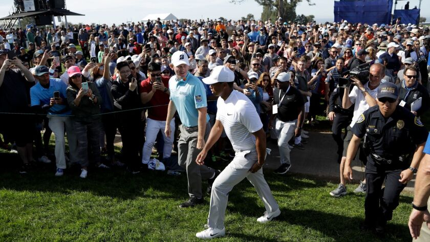 Tiger Woods, front, talks with Brandt Sneaker, left in blue shirt, as they make their way to the 14t