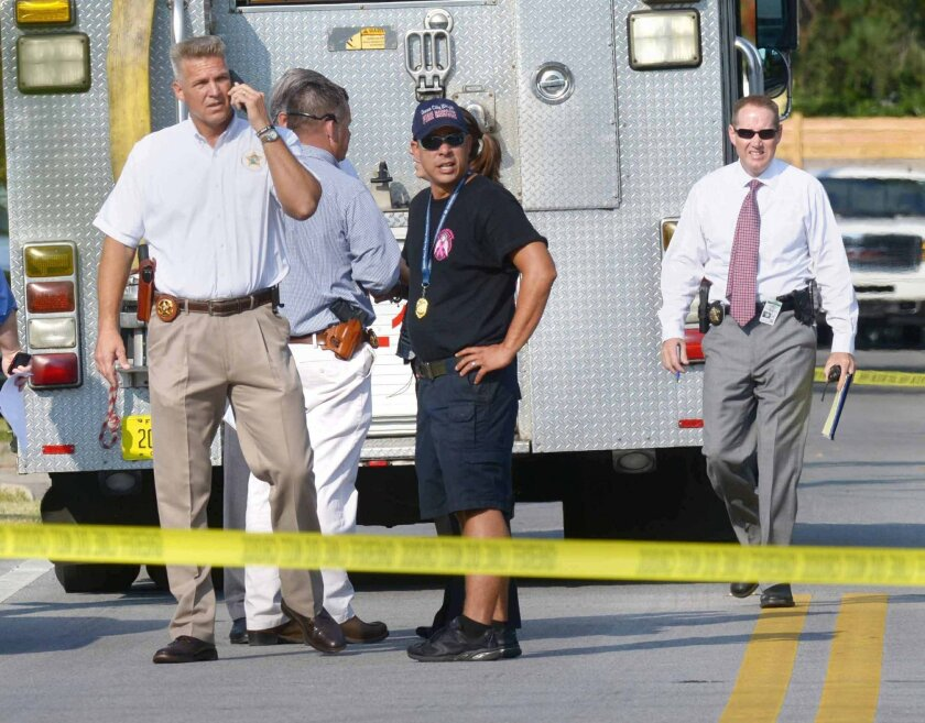 Okaloosa County Sheriff Larry Ashley, far left, and other sheriff's office personnel and emergency responders work at the scene of a law office in Shalimar, Fla., where a deputy sheriff was shot Tuesday, Sept. 22, 2015. The suspect then fled to the nearby town of Niceville and barricaded himself in a hotel before exchanging gunfire with deputies. He was taken into custody just before 10:30 a.m. Central time. (Devon Ravine/Northwest Florida Daily News via AP)