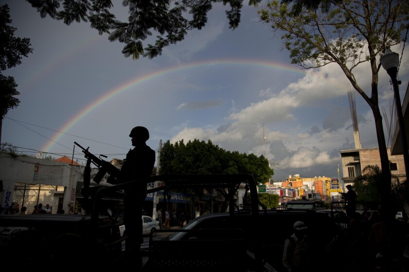 A rainbow forms a backdrop for a soldier standing guard in Iguala, in Mexico's Guerrero state, on Oct. 6.