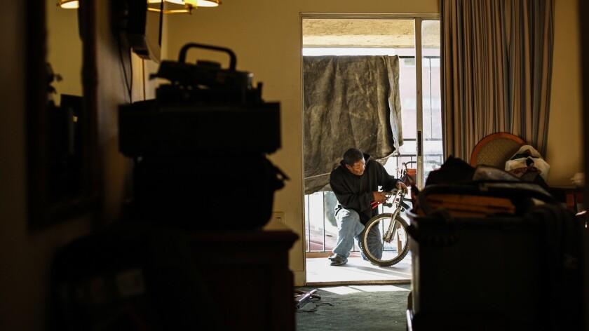 ANAHEIM, CA--MARCH 1, 2018: The bike man, Donahue Farrow works on a bike in his motel room's balcony