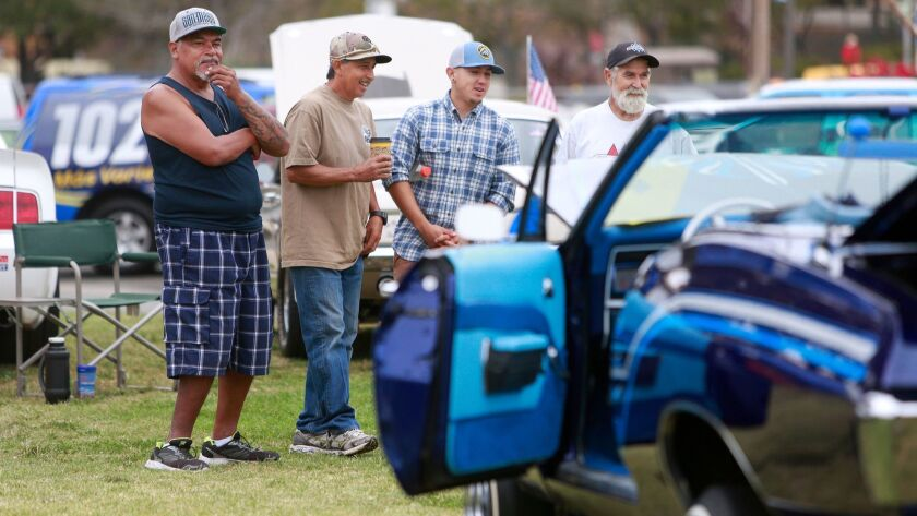 From left to right, Jose Aleman, David Diaz, his son David Diaz Jr. and Jonathan Knoebel admire some of the vehicles on display at the 25th annual Automobile Heritage Day Festival & Car Show in National City on Aug. 26, 2016.