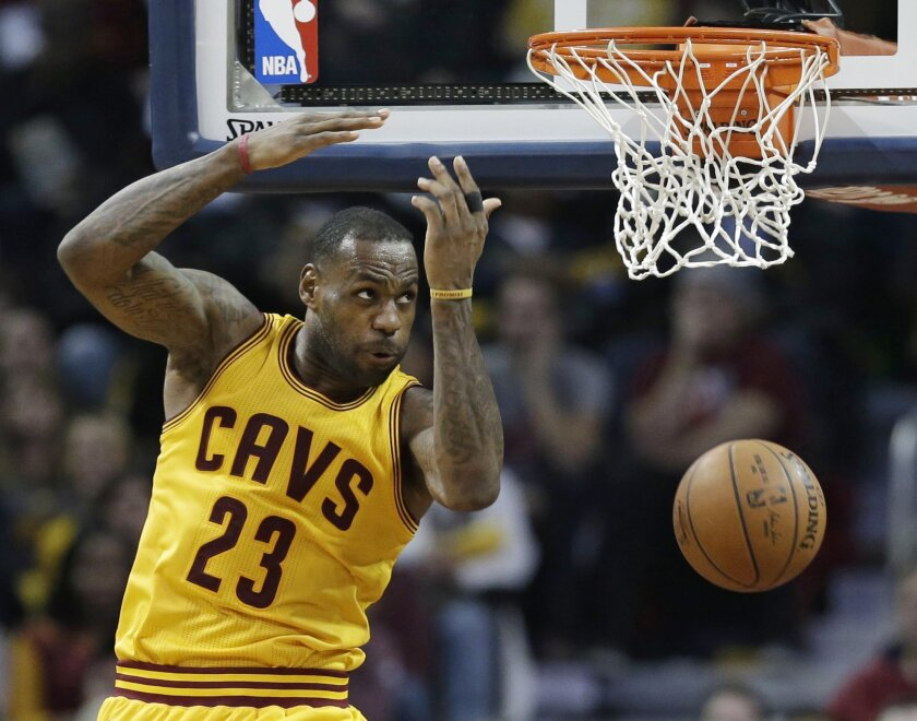 Cleveland Cavaliers' LeBron James looks back after dunking the ball against the Minnesota Timberwolves in the second half of an NBA basketball game Monday, Jan. 25, 2016, in Cleveland. The Cavaliers won 114-107. (AP Photo/Tony Dejak)