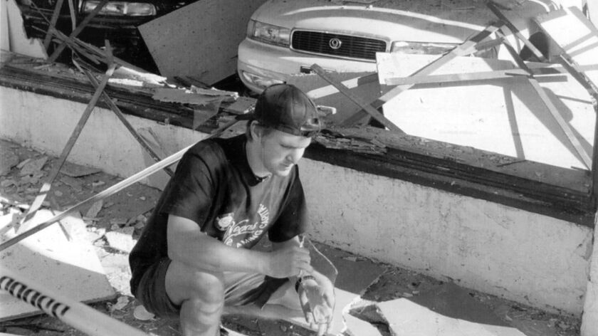 David Lane checks damage at a car dealership in Santa Monica after the Northridge earthquake.