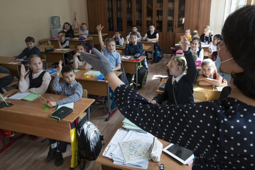 Children attend a lesson in a school in Moscow, Russia, Monday, Sept. 7, 2020. Russian schools, which switched to online classes in late March when the coronavirus pandemic swept the country, have reopened this month. (AP Photo/Pavel Golovkin)