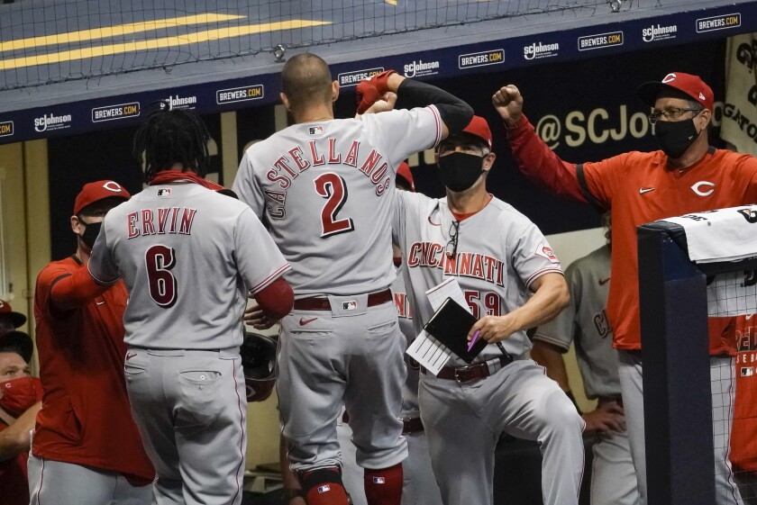 Cincinnati Reds' Nicholas Castellanos is congratulated after hitting a two-run home run during the sixth inning of a baseball game against the Milwaukee Brewers Friday, Aug. 7, 2020, in Milwaukee. (AP Photo/Morry Gash)