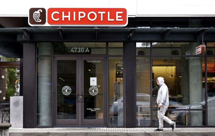 Una persona camina el lunes 2 de noviembre de 2015 frente a un restaurante Chipotle cerrado, en Seattle. Un brote de E. coli vinculado a los restaurantes Chipotle en el estado de Washington y Oregon ha enfermado a casi dos docenas de personas en el tercer brote de intoxicación por alimentos en la popular cadena de comida mexicana en lo que va del año. Se han rastreado casos de enfermedades bacterianas a seis de los locales de la cadena, pero como medida de precaución, la cadena cerró sus 43 establecimientos en las dos entidades de manera voluntaria. (Foto AP/Elaine Thompson)
