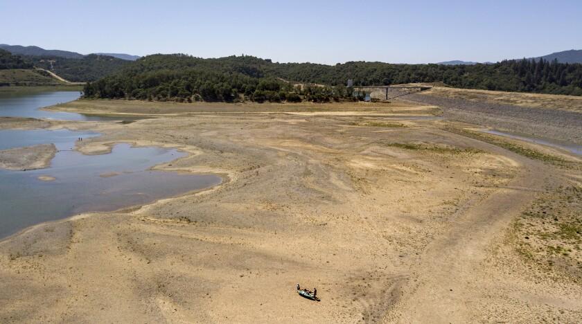 Kayakers make a long trek to the water at a drought-stricken Lake Mendocino.