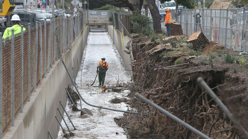 A member of the OC Public Works team walks a storm drain to observe debris in Laguna Canyon across f