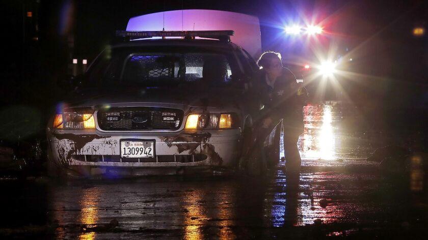 MALIBU, CALIF. - JAN. 5, 2019. A Sheriff's deputy works to free a atrol cruiser from mud covering