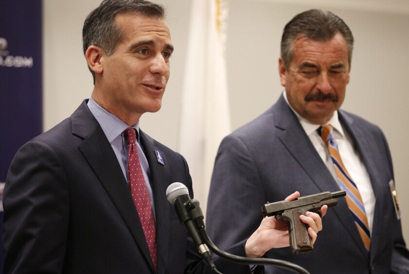Los Angeles Mayor Eric Garcetti holds a vintage pistol that was registered to Sammy Davis Jr., as he and L.A. Police Chief Charlie Beck discuss results from a gun buyback event this last weekend.