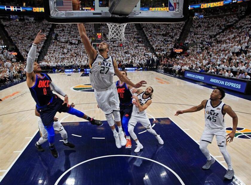 Rudy Gobert (c) de los Jazz en acción ante Russell Westbrook (i) de los Thunder, durante un partido de la NBA de la primera ronda de las eliminatorias de la Conferencia Oeste, entre los Utah Jazz y los Oklahoma City Thunder, en el Vivint Smart Home Arena de Salt Lake City (EE.UU.). EFE