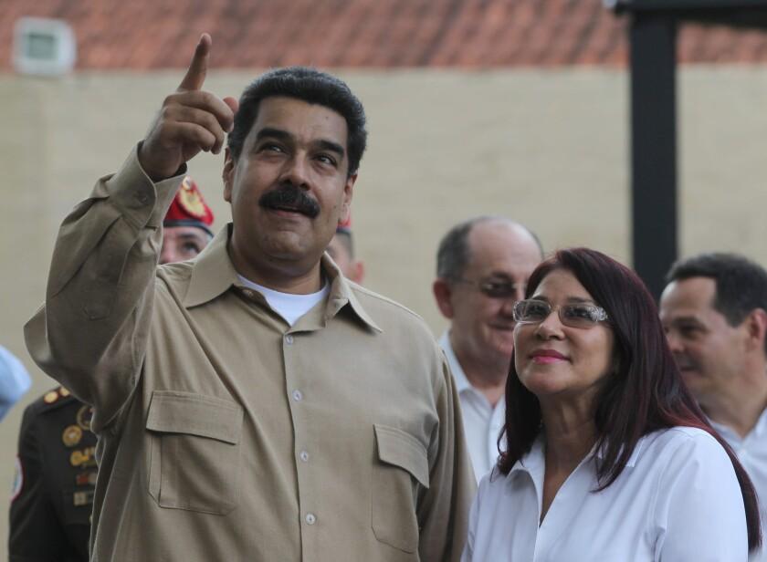El presidente venezolano Nicolás Maduro, izquierda, habla con su esposa, la primera dama Cilia Flores, mientras aguardan la llegada de su homólogo colombiano Juan Manuel Santos antes de una reunión entre ambos en Puerto Ordaz, Venezuela, el jueves 11 de agosto de 2016. (AP Foto/Fernando Llano)