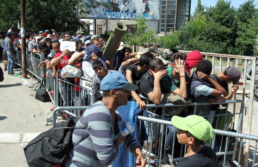 Migrants wait to be registered Aug. 25 at a refugee center in the town of Presevo in Serbia, where the number of daily arrivals is expected to reach 3,000 soon, the U.N. refugee agency reports.