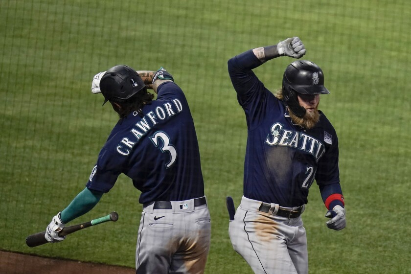 Seattle Mariners' Jake Fraley, right, celebrates his three-run home run with J.P. Crawford during the fourth inning of the team's baseball game against the Los Angeles Angels in Anaheim, Calif., Thursday, June 3, 2021. (AP Photo/Jae C. Hong)