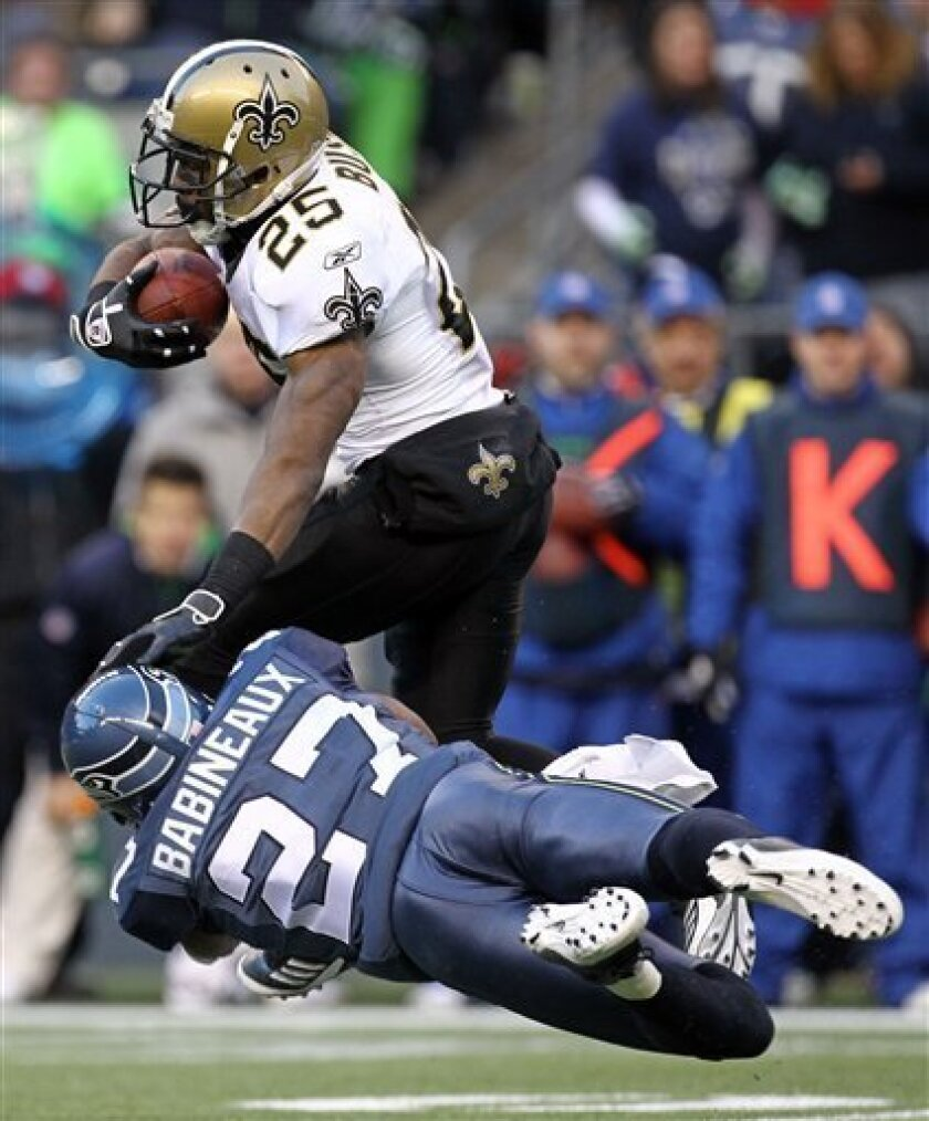 New Orleans Saints' Reggie Bush (25) is tackled by Seattle Seahawks' Jordan Babineaux in the second half of an NFL NFC wild card playoff football game, Saturday, Jan. 8, 2011, in Seattle. (AP Photo/John Froschauer)