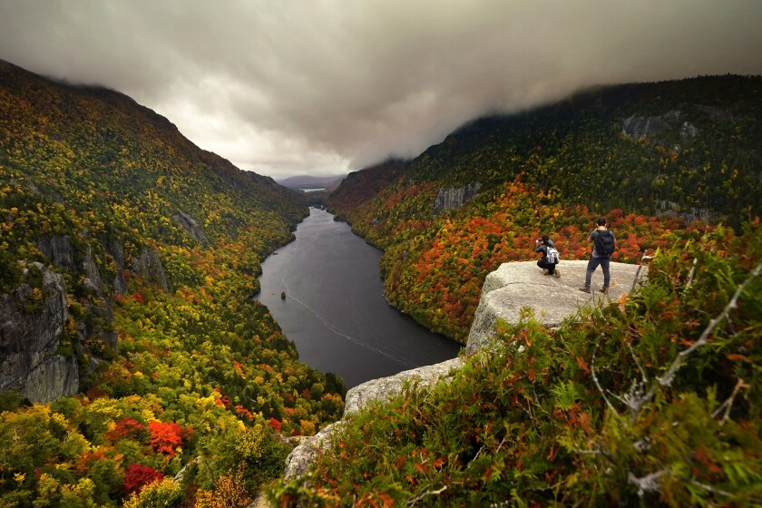 Two visitors photograph the in the colorful autumn view at the Indian Head vista overlooking Lower Ausable Lake in the Adirondacks, Sunday, Sept. 27, 2020, near Keene Valley, N.Y. (AP Photo/Robert F. Bukaty)