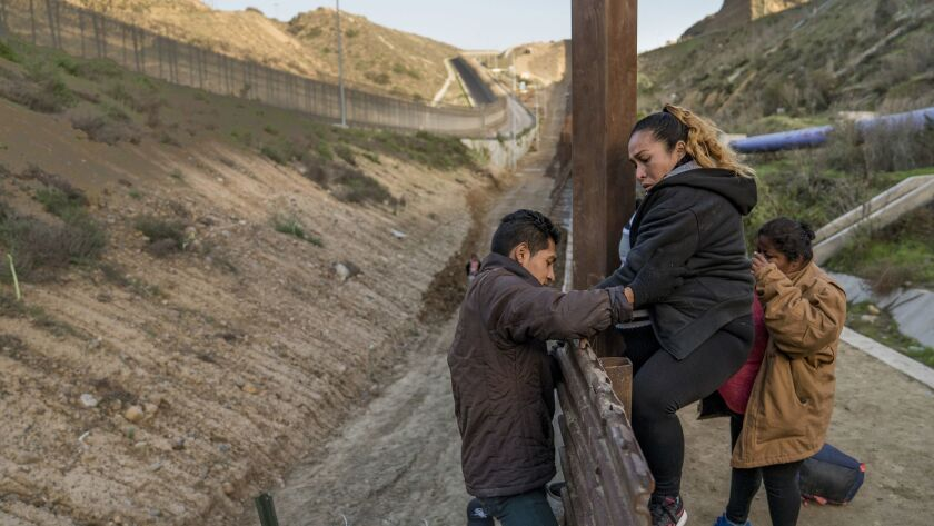 A pregnant migrant climbs the border fence from Tijuana, Mexico, Thursday, Dec. 27, 2018. Discouraged by the wait to apply for asylum at ports of entry, many Central American migrants from recent caravans are choosing to cross the border and hand themselves in to authorities.