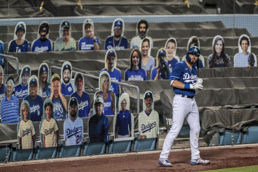 Dodgers second baseman Gavin Lux gets ready in the on-deck circle in front of cardboard cutouts of fans.