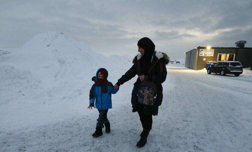 In this photo taken Thursday, Feb. 4, 2016 in Hammerfest, northern Norway, refugee Huda al Haggar and her son Omar from Sanaa in Yemen talk to the Associated Press at the northernmost refugee camp in the world. Waiting for their asylum claims to be processed, hundreds of people in emergency shelter