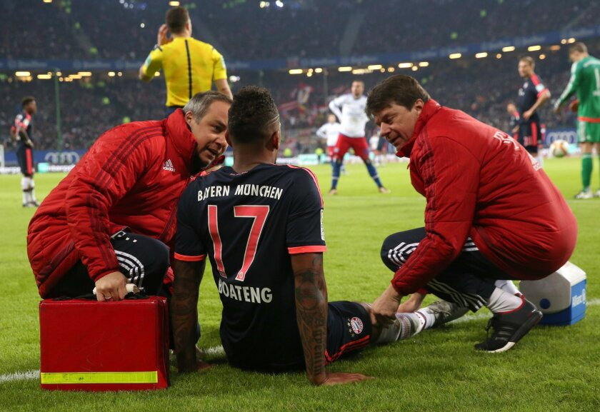 FILE - In this Jan. 22, 2016 file picture Munich's Jerome Boateng is treated by team doctor Volker Braun, left,  during the German Bundesliga football match between Hamburger  SV and Bayern Munich in Hamburg, Germany. Pep Guardiola's dream of leading Bayern Munich to the treble in his last season i