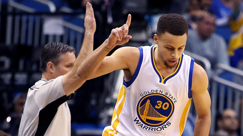 Warriors guard Stephen Curry celebrates after making a three-point shot against the Magic on Thursday night.