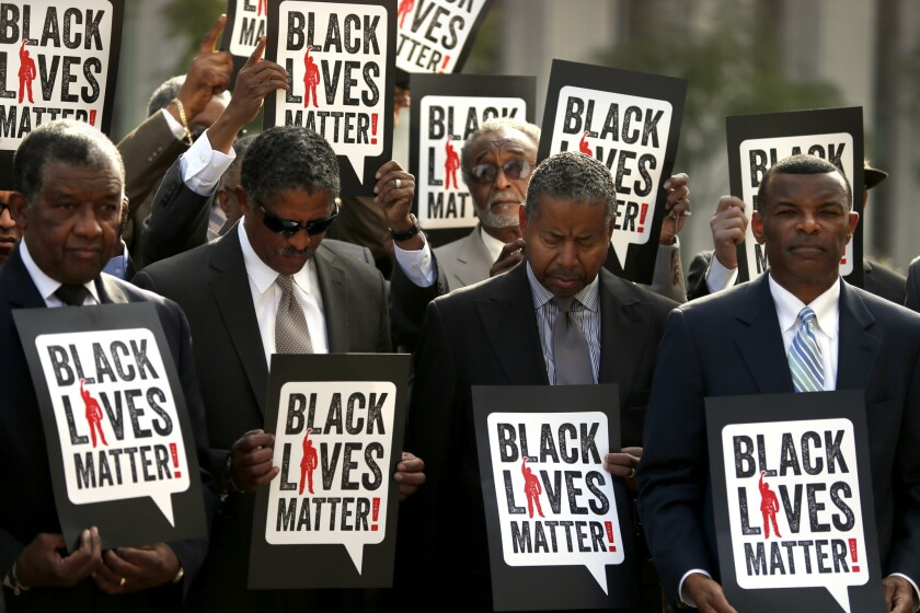 Participants in a silent vigil dubbed Suits in Solidarity stand on the steps of the U.S. Federal Courthouse in downtown Los Angeles on Monday.
