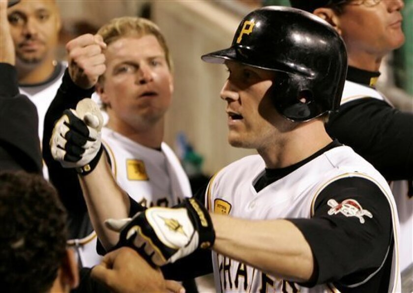 Pittsburgh Pirates' Jason Bay, right, is greeted in the dugout by teammates after hitting a two-run homer off St. Louis Cardinals pitcher Todd Wellemeyer in the fifth inning of baseball action at Pittsburgh Wednesday, April 23, 2008. (AP Photo/Gene J. Puskar)